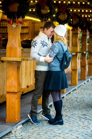 coronas de navidad: Víspera de Navidad. Cute joven pareja tiene buen momento en el bazar de Navidad. Los jóvenes se colocan cerca de mostrador de madera y suavemente abrazan. Puesto festivamente decorada con guirnaldas de Navidad y guirnaldas.