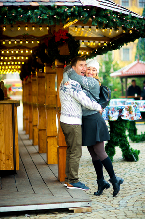 Eve of Christmas. Cute young couple has good time at the Christmas bazaar. Young people stand near wooden counter and joyfully embrace. Stall is festively decorated with Christmas wreaths and garlands