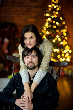 embracement: Christmas evening. Young woman embraces man sitting in a chair. In a room corner stands Christmas tree. She shines of fairy lights. Young people gently hold each other by hands. They look in camera.