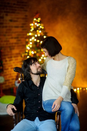 embracement: Christmas evening. Young woman embraces man sitting in a chair. She sits on an armrest. Young people with love look at each other. In a room corner stands Christmas tree. She shines in the twilight.