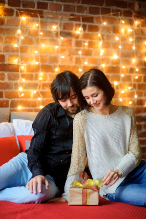 boxing day: Boxing day. The young couple sits having nestled to each other on a big bed. They look at beautifully packed box with the Christmas gift. The brick wall is festively decorated of fairy lights. Stock Photo