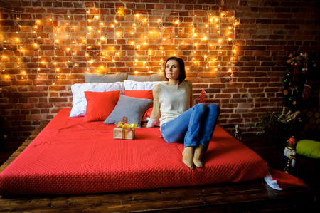 festively: Christmas. Cute young woman sits on a big bed with a dreamy look. Near her Christmas gift in beautiful packing. Room is festively decorated. In a corner of room flickering lights of Christmas tree.