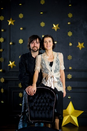 foretaste: Nice young couple stands against the background of festively decorated dark wall. Young man gently embraces the girlfriend. Woman is elegantly dressed. Young people with a smile look in the camera.