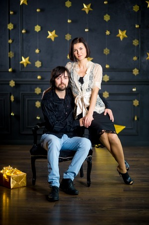 embracement: Young woman embraces man sitting in chair. She sits on an armrest. Dark wall of the room is decorated with gold garlands. On floor box with gift in gold packing lies. Young people look in the camera. Stock Photo