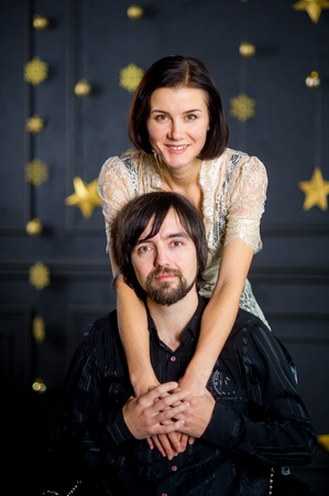 foretaste: Young woman gently embraces man sitting in a chair. The man holds the woman by hands.The dark wall of the room is decorated with gold garlands. Young people look in the camera.