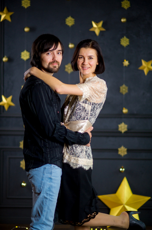 foretaste: Young married couple stand gently having embraced. Young man is serious, and woman happily smiles. They celebrate something. The dark wall is decorated with the shining garlands.