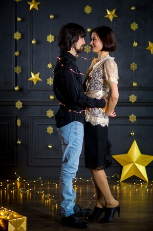 foretaste: Young married couple stand gently having embraced. Husband and wife look at each other with love and tenderness. They celebrate something. The dark wall is decorated with the shining garlands. Stock Photo