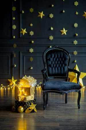 Waiting for a holiday. The beautiful velvet armchair is in festively decorated room. On a dark wall the gold shining garlands. Gifts in elegant boxes, festive accessories lie on a floor.
