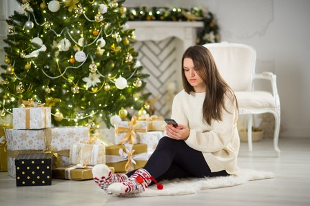 Christmas Eve. Nice girl sits near Christmas tree with mobile phone in hands. House is decorated by holiday. Under Christmas tree there are a lot of gifts. Girl sadly looks at the smartphone screen. Stock Photo