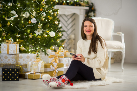 Christmas Eve. Nice dark-haired girl sits near Christmas tree with the mobile phone in hands. House is decorated by holiday. Under Christmas tree there are a lot of gifts. Girl joyfully smiles.