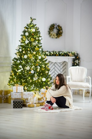 hung: Christmas Eve. Nice girl the brunette sits about the Christmas tree. She dreams of something. House is decorated by holiday. Under the Christmas tree a lot of beautifully wrapped up boxes with gifts.