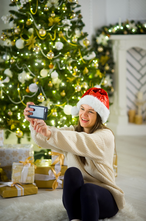 boxing day: Christmas. Lovely girl in Santas cap makes a selfie against the background of the Christmas tree. Under an elegant Christmas tree there are a lot of beautiful boxes with presents. Stock Photo