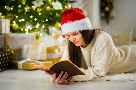 Cute girl the brunette in Santas cap. Beautifully decorated Christmas tree stands nearby. Elegantly decorated Christmas tree stands nearby. Beautiful boxes with gifts under the Christmas tree.