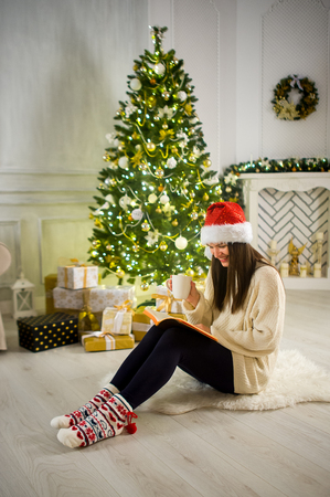 festively: Charming girl in Santas cap sits in the middle the room which is festively decorated by Christmas. Girl holds a cup and something reads. Under a beautiful Christmas tree there are a lot of gifts.