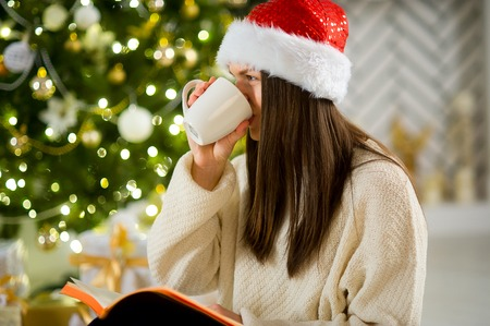 Girl in Santas cap drinks coffee near the Christmas tree. Girl has long dark hair. Before her open notebook. Girl has thought. Christmas tree shines sparks.