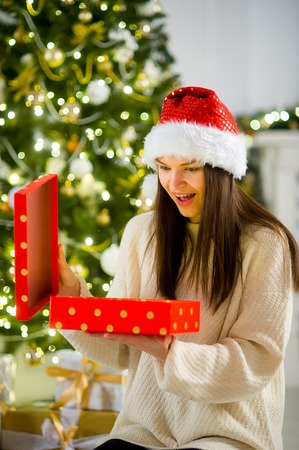 boxing day: Boxing day. Nice girl the brunette opening a box with the Christmas present. On her face joy. Behind the girl beautifully decorated Christmas tree.