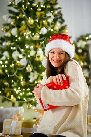 Lovely dark-haired girl in Santas cap presses to herself a box with the Christmas gift. Girl has a playful cheerful look. Against the background of beautifully decorated Christmas tree.
