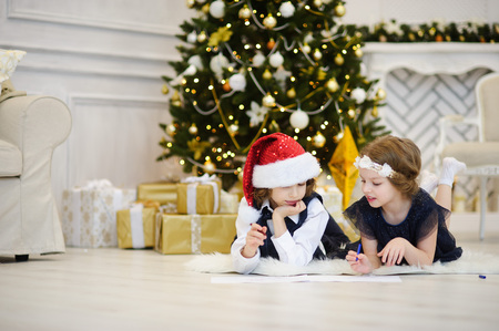 Christmas Eve. Children write letters to Santa Claus. Boy and girl of younger school age lie on a floor near the decorated Christmas tree. Children have thoughtful faces. House is festively decorated