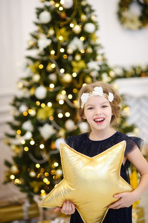 Portrait of the girl of younger school near the Christmas tree. The girl is dressed in a beautiful dark dress. On head of her a wreath. Girl holds in hand a pillow in the form of a gold star and laugh