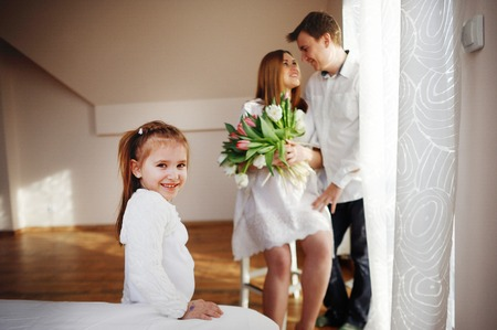 tender sentiment: Young man congratulates his pregnant wife. She sits in a beautiful white dress with a bouquet of tulips. Husband gently hugs a wife and lovingly looks at her. Little daughter looks in the camera.