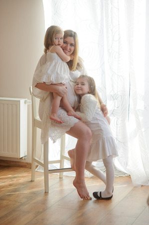 Beautiful pregnant woman with two daughters. Woman in a white dress sits on a chair. She keeps one little daughter on hands, second baby gently pressed to the belly of a pregnant mother. Stock Photo