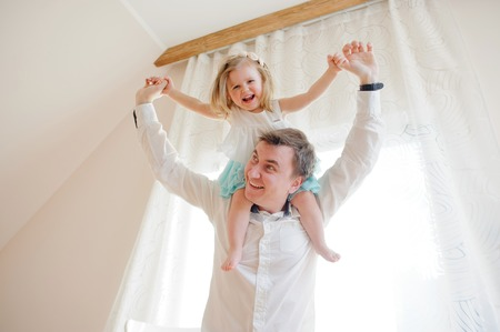 gaily: The young man gaily spends time with the little daughter. Charming baby sits on shoulders at the father and cheerfully laughs.