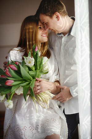 tender sentiment: Young man congratulates his woman. She sits in a beautiful white dress with a bouquet of multi-coloured tulips. Man tenderly embracing girlfriend and lovingly looks at her.