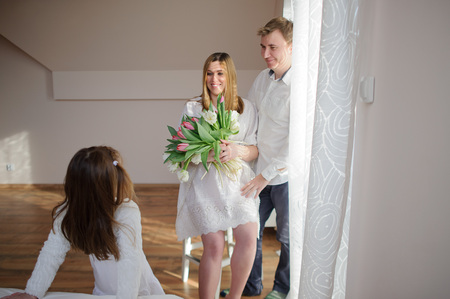 gently: Young man congratulates his pregnant wife. She sits in a beautiful white dress with a bouquet of tulips. Husband gently hugs a wife and lovingly looks at her. Little daughter looks at the parents.