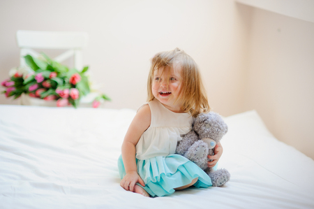 The charming little girl sits on a big bed. In hands at the baby a gray teddy bear. The girl has a cheerful playful look and the hair tousled from a play.