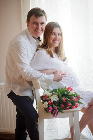 tender sentiment: Young man congratulates his pregnant wife. She sits in a beautiful white dress with a bouquet of multi-coloured tulips. Husband tenderly hugs his beloved.