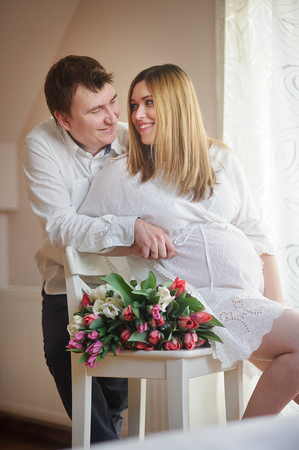 tender sentiment: Young man congratulates his pregnant wife. She sits in a beautiful white dress with a bouquet of multi-coloured tulips. Husband tenderly hugs his beloved and lovingly looks at her.