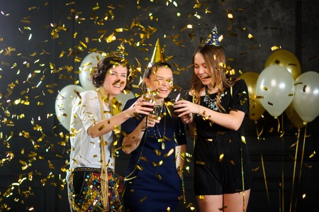 elegantly: Three young women celebrate something. In hands at everyone a glass with champagne. They are elegantly dressed. From above on girlfriends the gold confetti falls. The room is decorated with balloons.