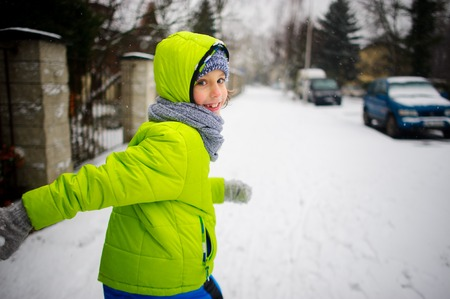 Little schoolboy goes down the street in winter day. The boy is dressed in a bright ski suit. It is snowing. The child likes such weather. He cheerfully smiles. Stock Photo