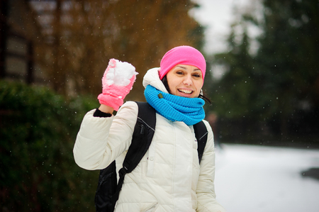 Charming young woman holds a snowball in hand. She is ready to throw him into someone. Woman is dressed in a bright cap, a scarf and gloves. It is snowing. Woman smiles.