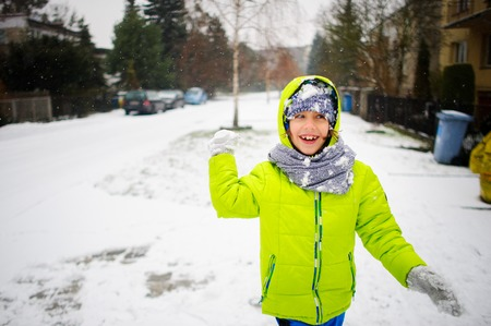 The cheerful boy of school age plays snowballs. The boy is dressed in a bright ski suit. It is snowing. To the boy it is very cheerful. Stock Photo