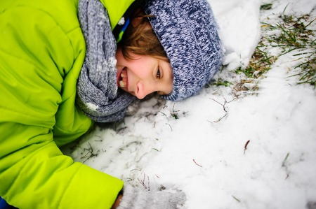 christmas grounds: Cheerful boy of school age in a bright ski suit lies on snow . The first snow has hardly covered the earth in the park. The grass and dry leaves is visible. But children very much love winter and snow.