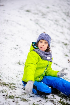 The boy of school age in bright winter overalls sits on the ground which is slightly covered with the first snow. Through snow the grass is visible. The boy rejoices. Children adore winter and snow. Stock Photo