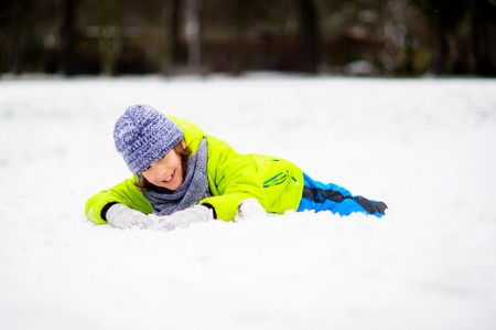The boy of school age in bright winter overalls lies on snow. He has an excellent mood. Children adore winter and snow.