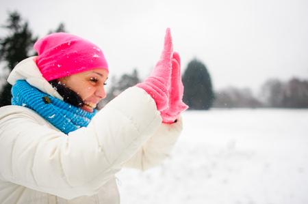 Okouzlující mladá žena hraje s někým v sněhových koulích. Skryje tvář v ruce. Pro ženu je velmi veselá. Ona je oblečená do jasného lyžařského obleku.