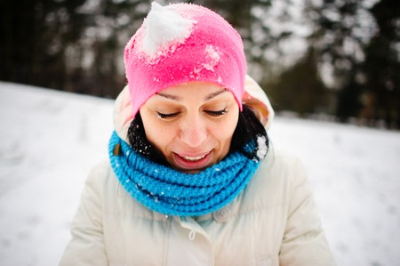 Charming young woman plays with someone in snowballs. The first snow and winter entertainments very much please. The bright hat is closed up with snow. The woman happily smiles. Stock Photo