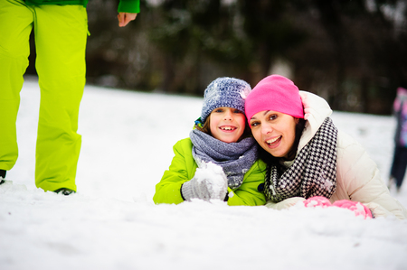 prank: Charming young woman and her son cheerfully spend time in the winter park. They are dressed in bright warm ski suits. Both look out because of a big snowdrift also smile. On walk they are not one. Stock Photo