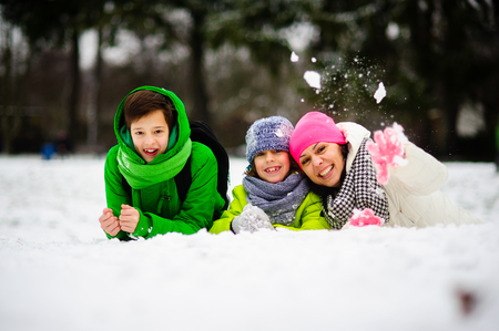 Young woman and two of her sons cheerfully spend time in the winter park. They are dressed in bright warm ski suits. All look out because of a big snowdrift. Mother throws into someone a snowball. Stock Photo