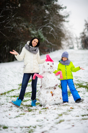 Mother with son have built snowman. Grass in park is slightly covered with snow. But charming young woman and her child are very glad to first snow. Snowman has turned out dirty, but very ridiculous.