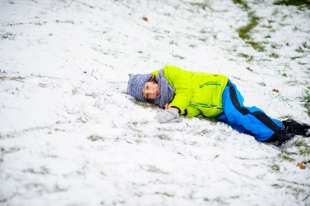 hardly: The child in a bright ski suit alone lies on snow . The first snow has hardly covered the earth in the park. The grass and dry leaves is visible. Stock Photo
