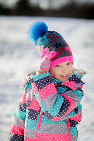 corrects: Winter portrait of girl of younger school age. Child is warmly dressed in a bright motley jacket and a cap. Mittens on hands. Girlie corrects a cap. Against the background of snow. Stock Photo