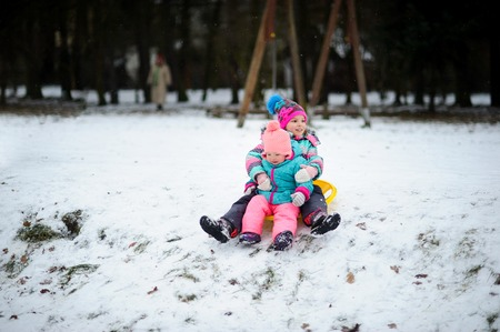 hardly: Two little girls together move down from a hill on the saucer sled. In the winter park it is snowing. Children are dressed in warm and bright ski suits. The earth is hardly covered with the first sno