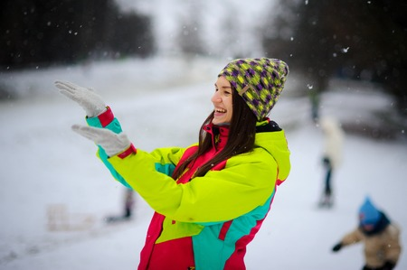snowdrifts: The young woman joyfully holds up palms under the falling snow. She on walk in the winter park. The woman is dressed in a bright jacket and knitted gloves and a cap. The falling snow causes delight. Stock Photo