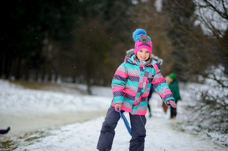 The girl of younger school age spends time in the winter park with pleasure. She is going to move down once again from a hill on the sheet sledge. It is snowing. The child has a happy look. Stock Photo