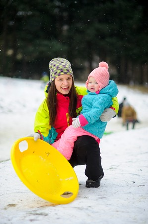 Mother with little daughter have come to ride the sledge to winter park. Both are dressed in bright warm ski suits. Woman holds the yellow saucer sledge in hand. It is snowing.