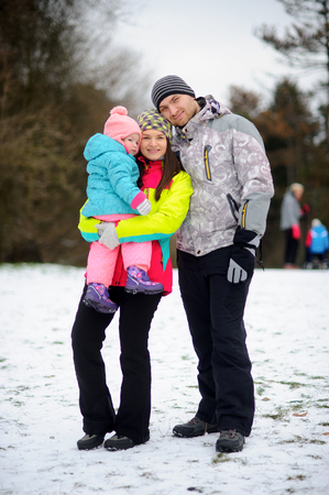 embraced: Winter family portrait. Young couple with little daughter against the background of the winter park. Family stands having embraced. Man and woman smile. Baby has a serious look.